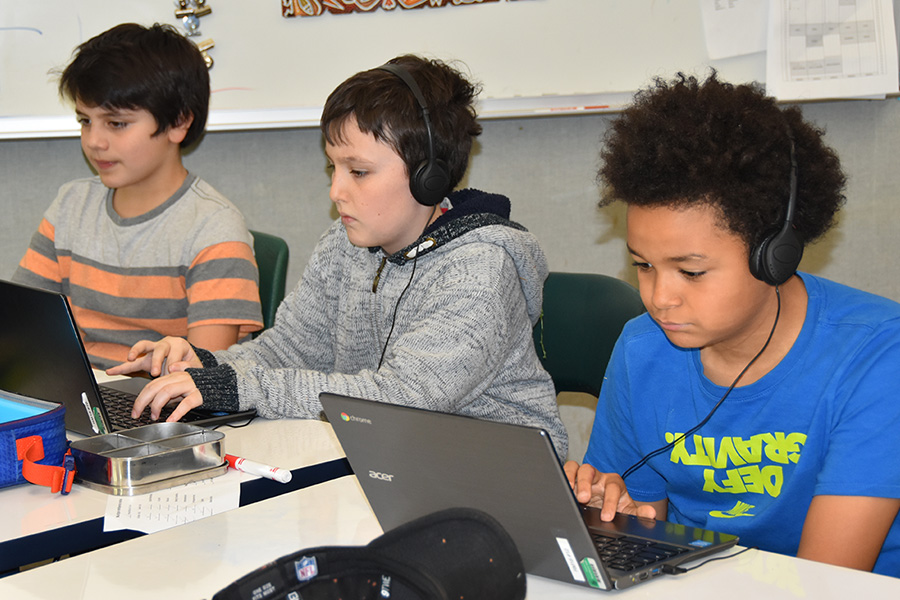 5th grade boys working on digital parent-teacher conference website presentations