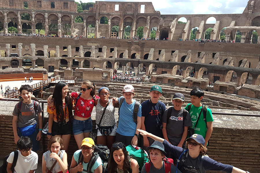 Middle School students on Italy trip pose in front of the Colosseum in Rome, Italy