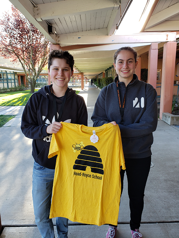 2 smiling upper school girls holding yellow custom-made Head-Royce CA JCL State Latin Convention tee