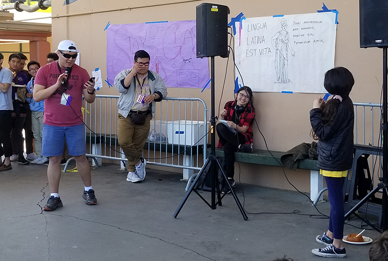 Head-Royce middle school girl holding mic in competition during Roman Rap Battle