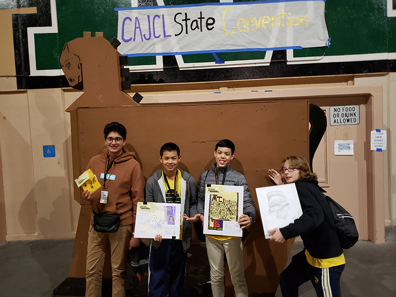 4 Head-Royce middle school boys stand with artwork in front of Trojan horse replica